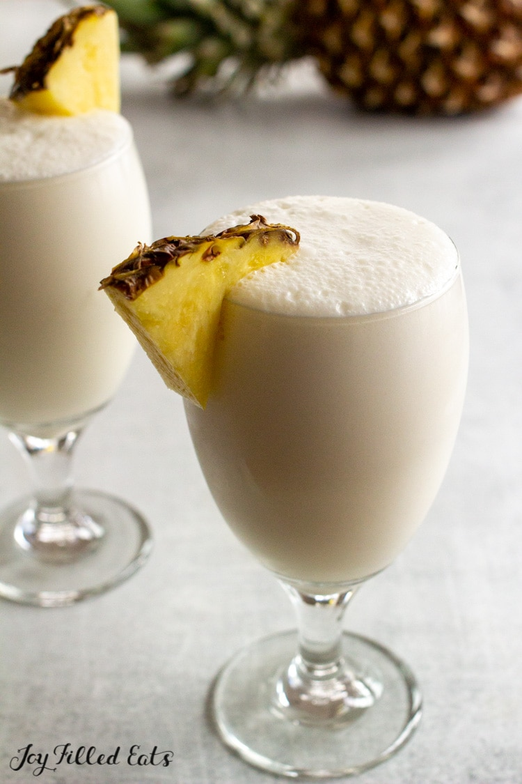 two glasses of pina colada with sliced pineapple garnish
