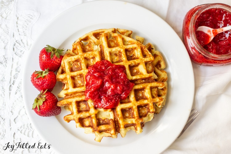 stack of vanilla protein waffles with almond flour topped with strawberry jam and severed with a fork and whole strawberries