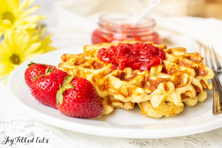 protein waffles topped with strawberry jam set on a plate with a fork and whole strawberries