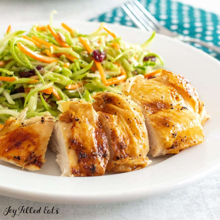 sliced chicken on a plate with broccoli slaw