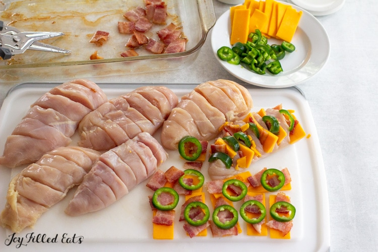 bacon cheese jalapeno slices and sliced chicken breasts on a cutting board