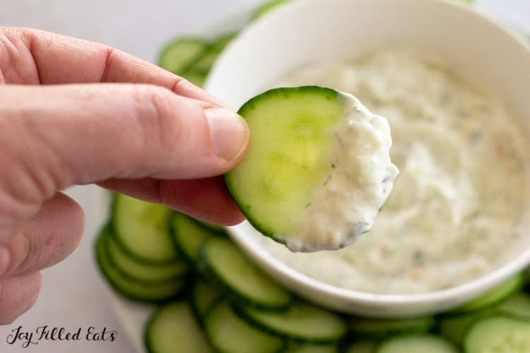 hand dipping cucumber into keto tzatziki sauce