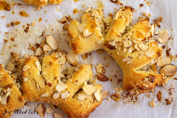 close up of the almond bear claws on a parchment lined baking sheet