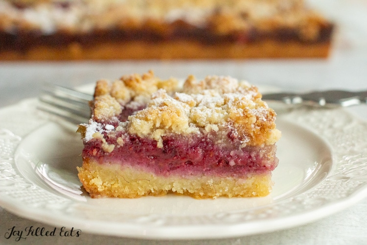 one of the keto raspberry jam bars on a plate with a fork
