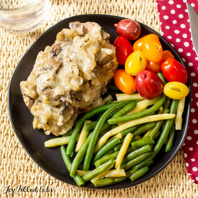 overhead shot of one of the keto smothered pork chops on a plate with green beans and tomatoes
