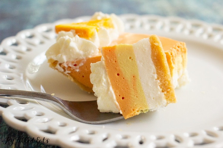 bite of orange creamsicle cheesecake on a plate with a fork