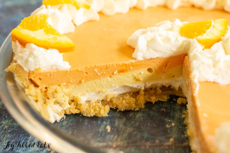 no bake orange creamsicle cheesecake in a glass pie plate missing a slice