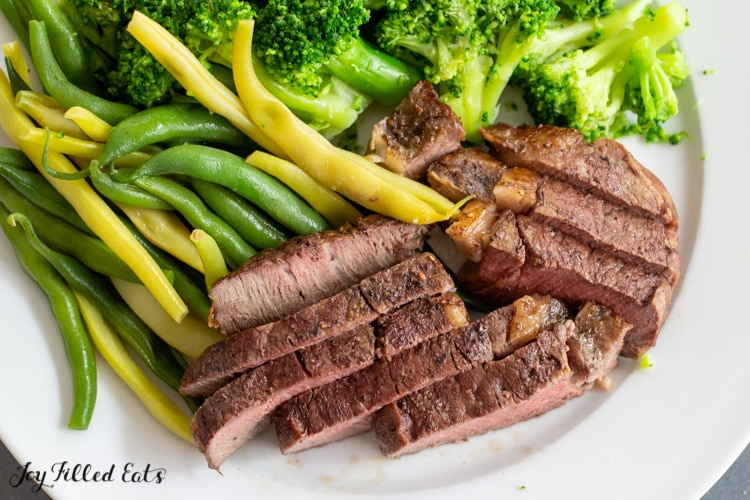 air fryer filet mignon sliced on a plate with vegetables