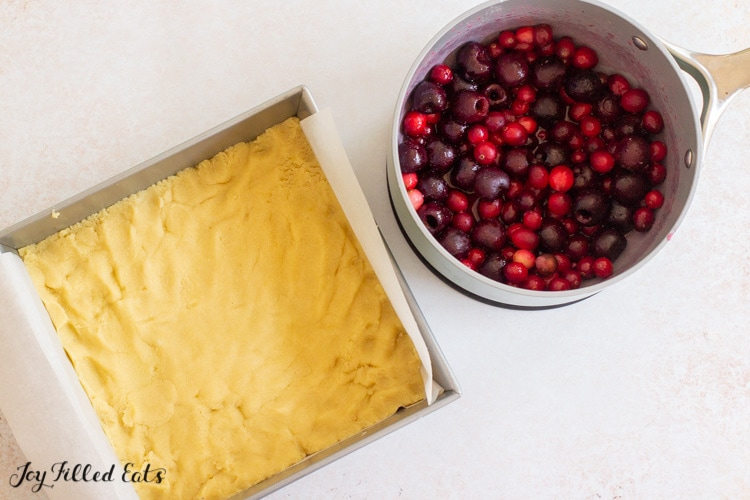 crust in pan and saucepan with cherries and cranberries