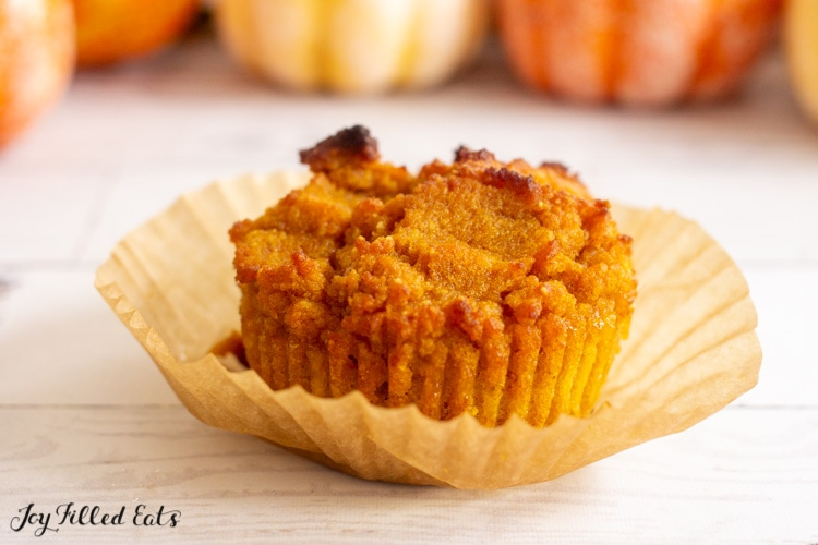 one of the keto pumpkin muffins sitting on a paper liner