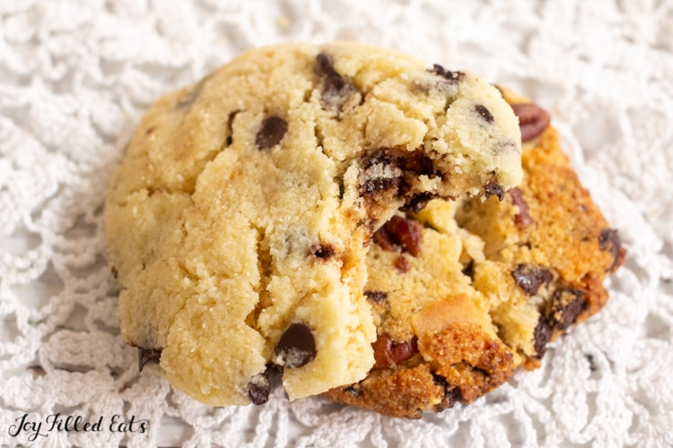 chocolate chip cookie missing a bite sitting on a pecan cookie