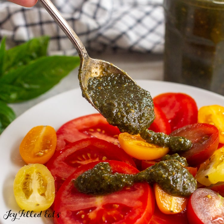 spooning pesto sauce on top of tomatoes