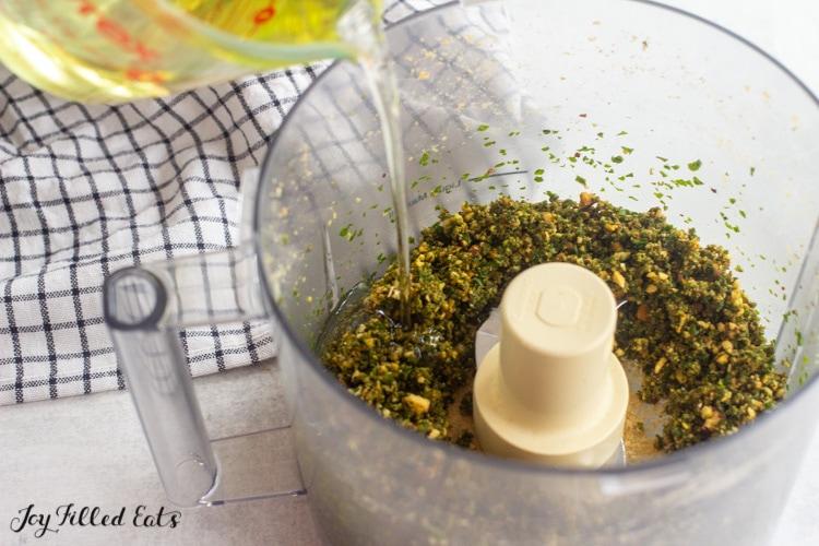 adding oil to the almond basil pesto