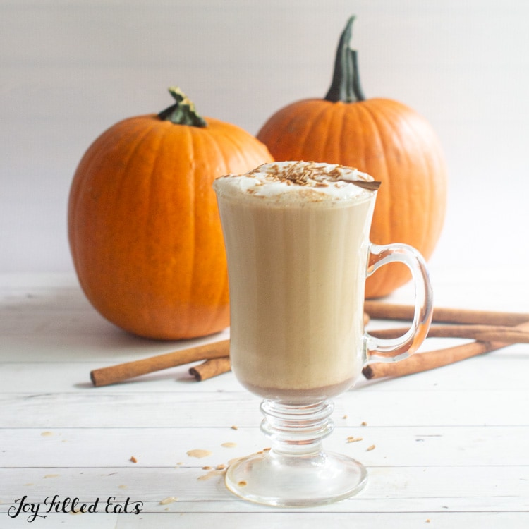 tall glass of keto pumpkin spice latte with pumpkins and cinnamon sticks in the background