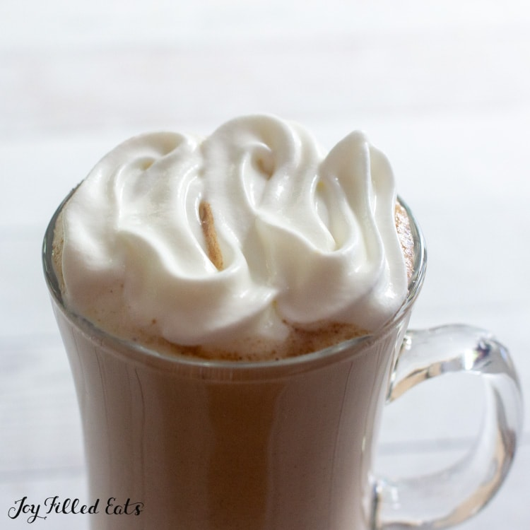 topping a keto pumpkin spice latte with whipped cream