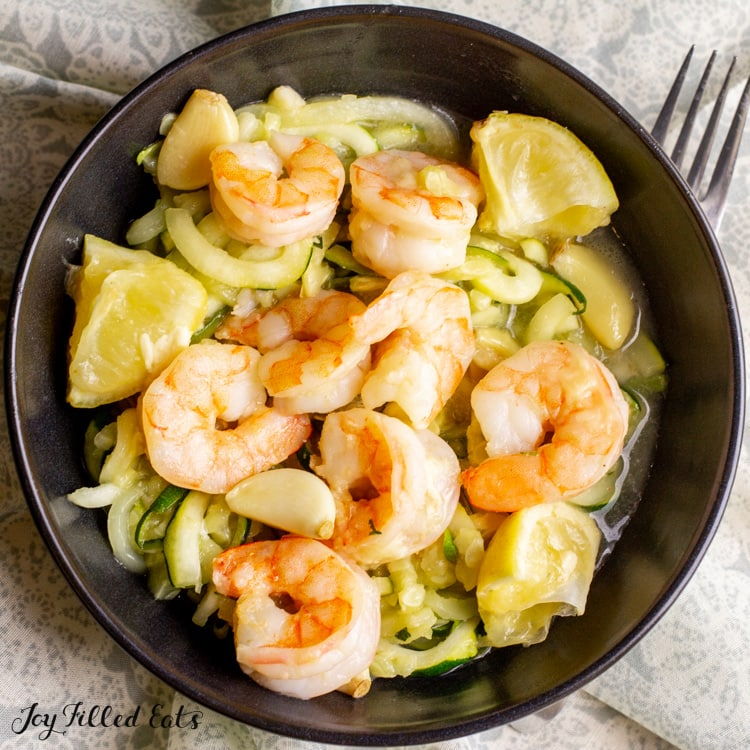 overhead view of black shallow bowl filled with keto shrimp scampi and lemon wedges topped on zucchini noodles