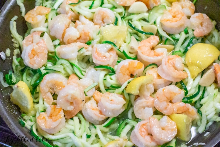 shrimp, lemon wedges and zucchini noodles close up cooking in a skillet