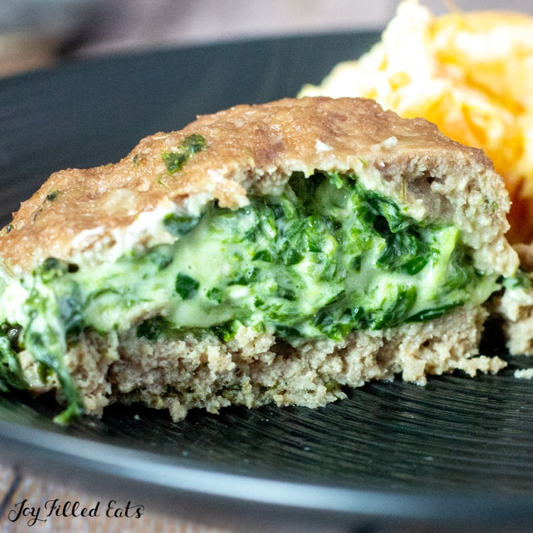 close up of stuffed turkey burger with spinach and three cheeses cut in half on a black plate