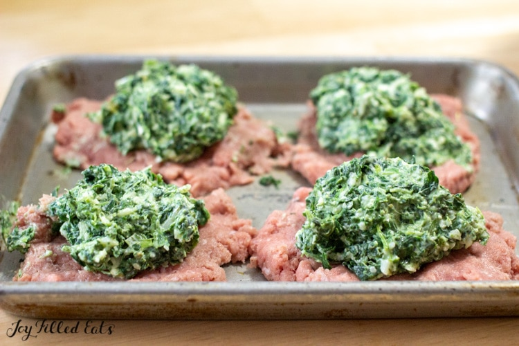 four patties topped with spinach and three cheese filling on a square baking dish